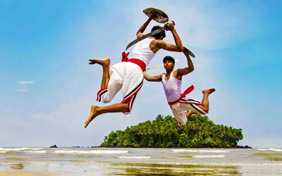 Artists performing Kerala's oldest traditional martial art form Kalaripayattu on a beach in Kerala, India