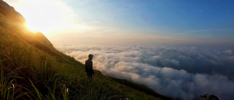 A Man Standing On Field Against Cloudscape During Sunset in Kerala hill station