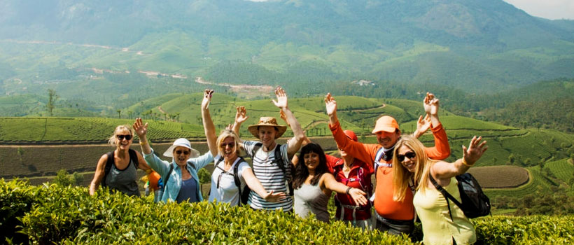 A wide-view shot of a multi-ethnic group of friends standing next to the Munnar tea plantations in Kerala