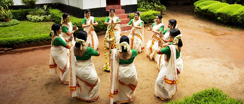 Group of Women performing the Thiruvathirakali dance in front a home during the occasion of Onam festival