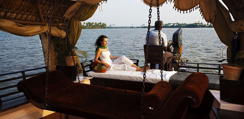 A woman lying in Kerala houseboat and enjoying the houseboat tour in backwaters of Kerala