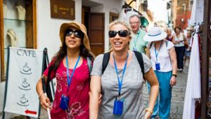 A front-view shot of a multi-ethnic group of tourists walking down a narrow street in Fort Kochi, Kerala.