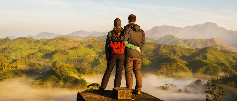 View of a couple standing and a valley in the background with fog and tea plantations at sunrise in Munnar, Kerala, India