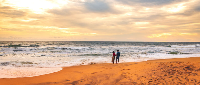 A lovely young couple enjoying the sunset in Snehatheeram beach near Thrissur, Kerala
