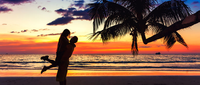 Couple kissing on the beach with a beautiful sunset in background, man lifting the woman on background sea ocean water and colorful sunset